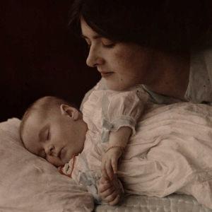 Äiti katsoo nukkuvaa lasta
