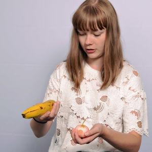 Siiri Kinnari punnitsee kädessään banaania ja omenaa.