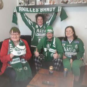Två kvinnor och två män sitter i en soffa. De har gröna accessoarer och håller upp en halsduk där det står Akilles.