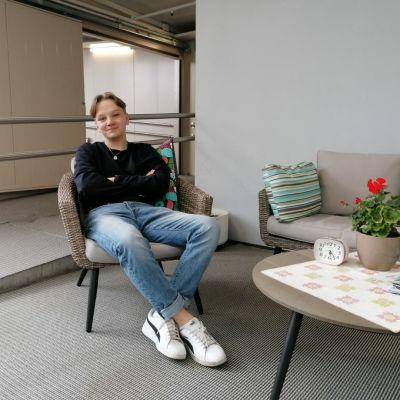 Oscar Björkell sitter i en stol och ser glad ut
