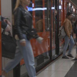 Ihmiset liikkuvat metroon asemalaiturilla
