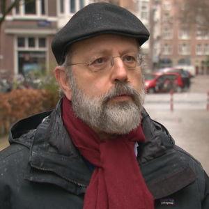 Professor Jonathan Zeitlin. Han är en man i medelåldern. Bilden är tagen utomhus. Det är fortfarande tidig vår i Amsterdam och det regnar.
