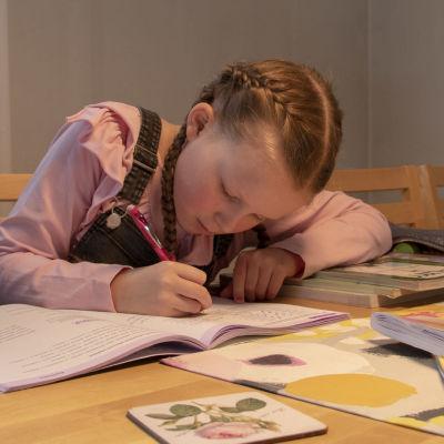 lapsi tekee koulutehtäviään kotona