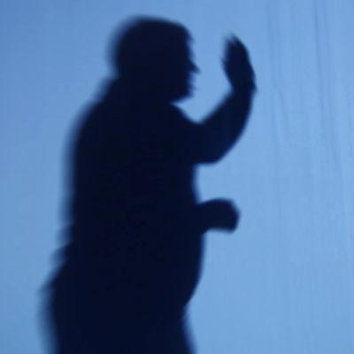 Skuggor av man och kvinna. Mannen höjer handen för att slå.