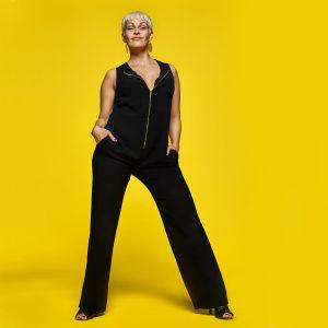 Asennemuija Jenni Janakka seisoo kuvassa mustissa haalareissa, keltainen tausta.