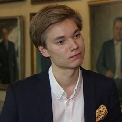 Vinnaren av Ekonomiguru-tävlingen år 2017, Jooa Mustonen, intervjuas med några tavlor i bakgrunden.