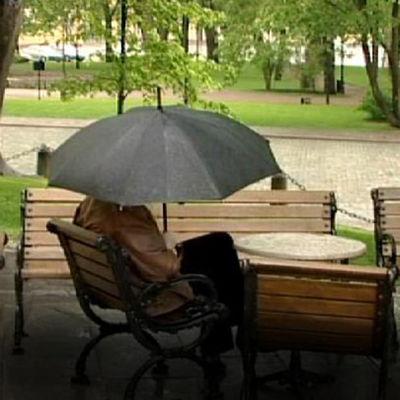 Mies isuu puiston penkillä mustan sateenvarjon alla