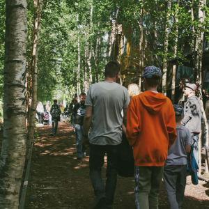 Människor promenerar på festivalområde mellan träd och en vägg med graffitimålningar.