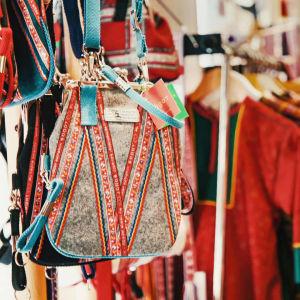 Kirjailtu käsilaukku lähikuvassa, taustalla värikkäitä kirjottuja vaatteita myymälässä.