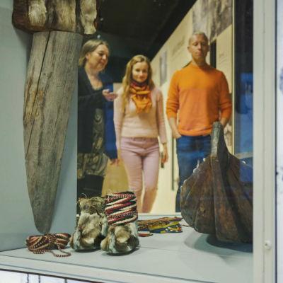 Vitrin med skoltsamernas föremål: liten träbåt, rep, och traditionella pälsskor. I bakgrunden tre personer som tittar på sakerna.