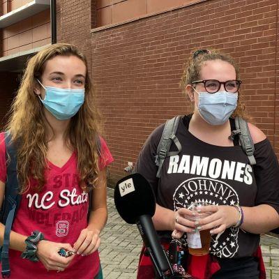 Tre personer med munskydd på står framför en röd tegelvägg vid ett förhandsröstningsställe i North Carolina.