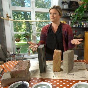 Camilla Forsén-Ström visar upp tegelstenar och roman på ett bord.