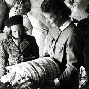 Nainen ja lapsia tuomassa lumppuja