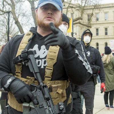 Aseella varustautunut mielenosoittaja Michiganin pääkaupungissa Lansingissa