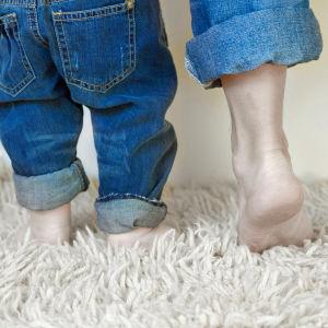 Isän ja pienen lapsen jalat matolla, kummallakin farkut jalassa.