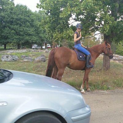 En bil kör förbi en häst och en ryttare.