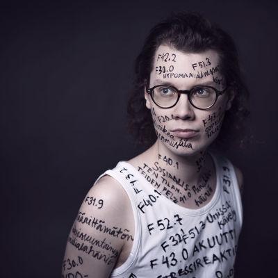 PItkähiuksisen radiotoimittaja Jani Tanskasen kasvoille ja iholle sekä hihattomaan paitaan on kirjattu psykiatristen diagnoosien nimiä ja koodeja tautiluokituksesta ICD-10.