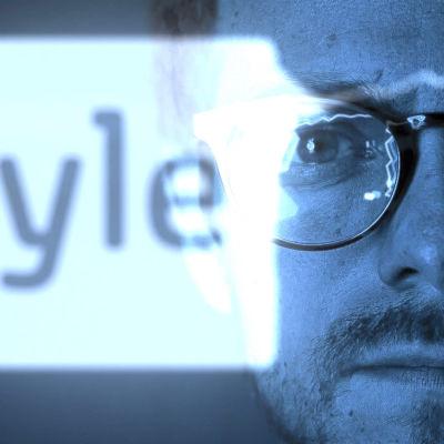 Ylen data -artikkelin pääkuva, mies katsoo kuvaan ja yle logo loistaa taustalla