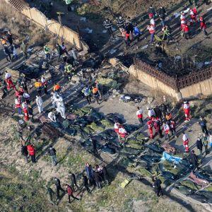 Bild uppifrån av olycksplatsen i Iran där ett Ukraine International-plan störtat. Räddningsarbetare går omkring och likpåsar ligger på rad.