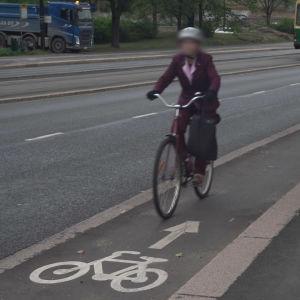 En kvinna kör med en cykel på ett enkelriktat cykelfält i fel riktning. I bakgrunden syns en spårvagn.
