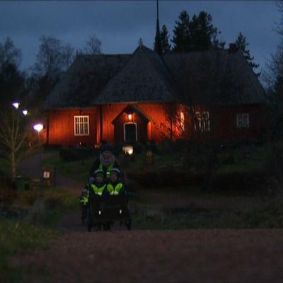 Daghemsbarn körs på en lådcykel med elmotor vid en kyrka i gryningen