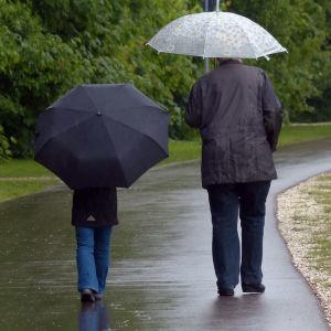 Mies ja lapsi kävelevät sateenvarjojen alla sateisessa puistossa.