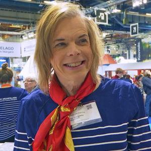 Tanja von Knorring på resemässa med en scarf runt halsen och leende tittande förbi kameran.