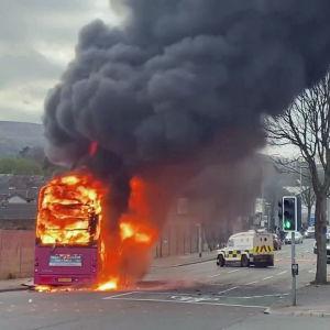 En röd tvåvåningsbuss brinner på en gata.