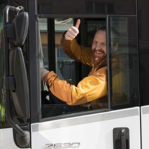 Tommi Manninen istuu jäteauton kuljettajan paikalla ja näyttää peukkua.