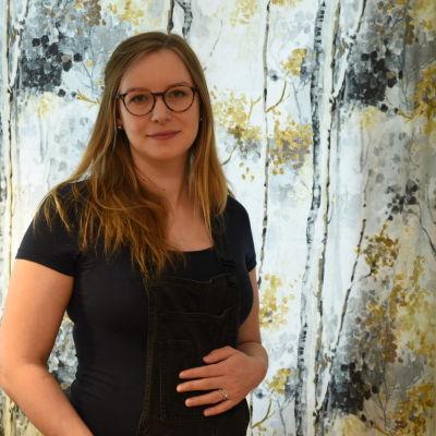 Victoria Hartman tittar in i kameran och håller handen på sin gravida mage