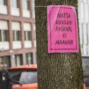 """Nainen ripustaa puuhun kylttiä """"Natsa kuuluu roskiin, ei maahan"""""""
