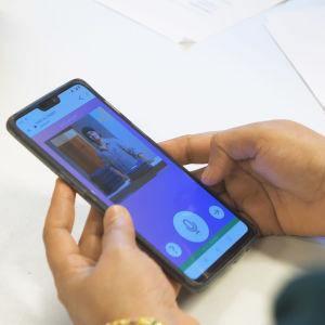 ihminen pitää käsissään kännykkää jonka ruudulla kielikylpy 2.0 sovellus