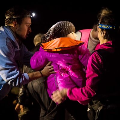 Kaksi otsalampuilla varustautunutta ihmistä kantaa lasta pimeällä.