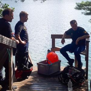 Räddningspersonal står på en brygga vid sjön.