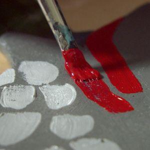 Pensel som målar dekorationer i rött.