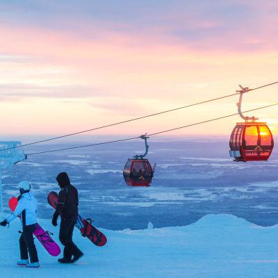 Näkymä Ylläksen laskettelurinteen päältä, kuvassa oikealla hiihtohissejä, vasemmalla ihmisiä lasketteluvarusteineen.