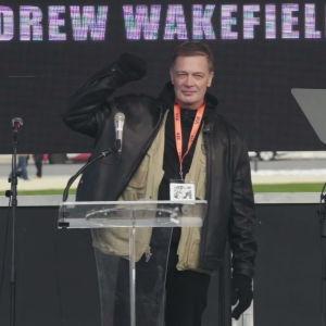 Äldre man i svart läderjacka står på en scen och lyfter knytnäven som segertecken. I bakgrunden står det Andrew Wakefield.