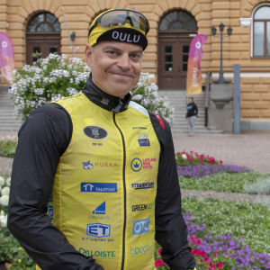 Romppainen seisoo Oulun kaupungintalon edustalla hymyillen kameralle