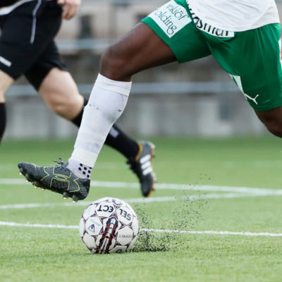 Fotbollsspelare och boll på konstgräs.