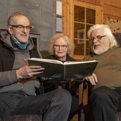 Reino Kuivalainen, Sirpa Sulopuisto ja Heikki Turunen lukevat leikekirjaa taiteilijatalo Hupelissa.