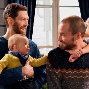 Två leende vuxna män med varsitt barn i famne eller på ryggen.