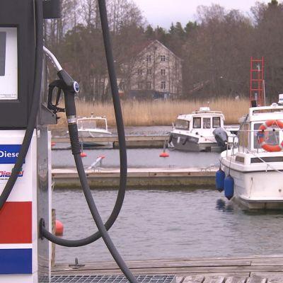 En bränslepump på en brygga, en fritidsbåt står förtöjd i bakgrunden.