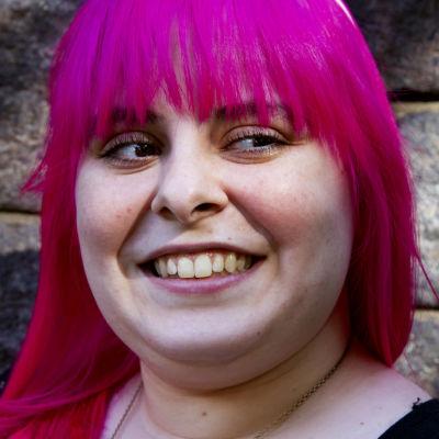 Felicia Prehn hymyilee tiilimuurin edessä.