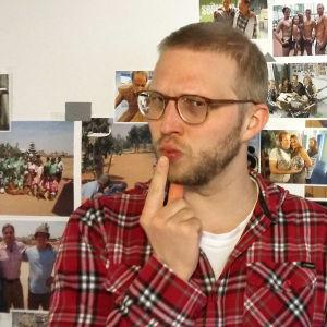 Toimittaja Nuutti Takkinen mietteliäänä Puoli seiskan valokuvaseinän edessä