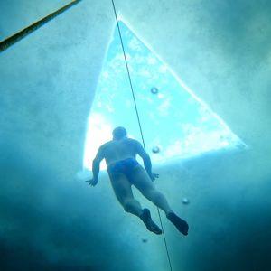 En man i vattnet under isen. Ovanför honom syns ett triangelformat hål i isen.