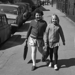 Kolme tyttöä koululaukkuineen kävelemässä Neljännellä linjalla kohti Porthaninkatua.
