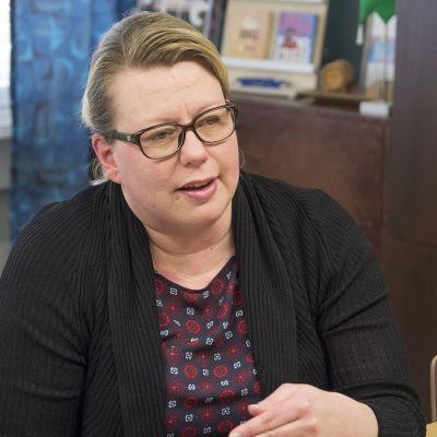 Anu Tervonen puhuu toimittajalle pöydän äärellä.