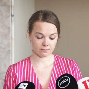 Katri Kulmuni står vid mikrofoner, läser från ett papper.