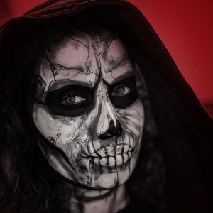 Lähikuvassa nainen, joka on pukeutunut kuolemaksi. Tausta on kuvakäsitelty punaiseksi.