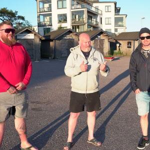 tre män framför bodar